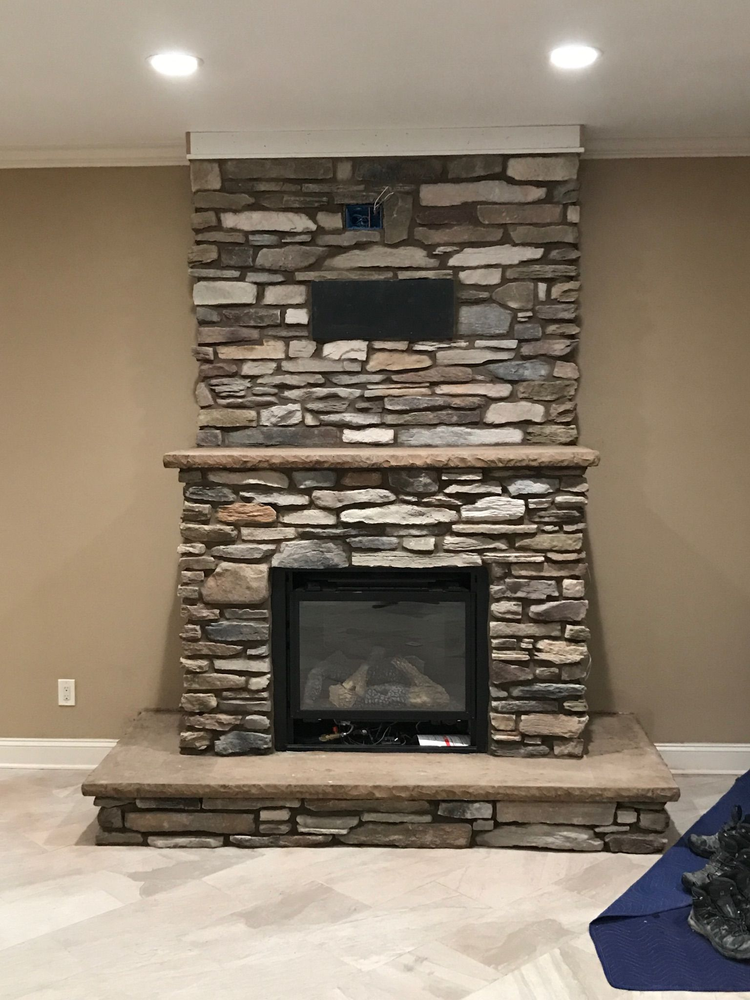 gas fireplace insert with cultured stone veneer and stamped