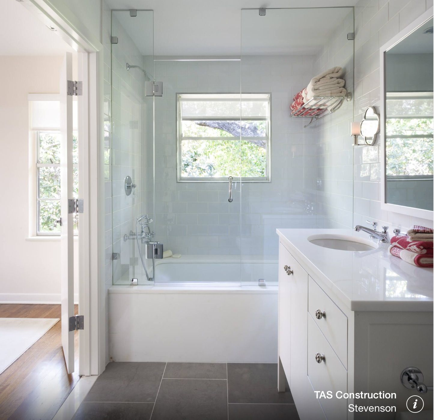 Shower over bath with glass door and window. Dark floor and white ...