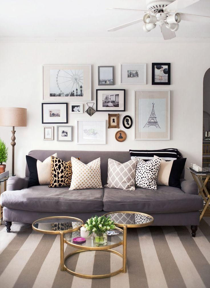 Gallery wall over the sofa with black and white prints a striped neutral rug and mixed print throw pillows a stylish way to prove that neutrals never
