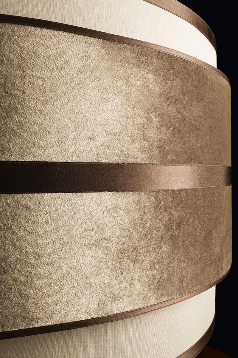 Detail of the Tamburo lighting collection by Oasis, a basic, simple shape of a white sand cotton cylinder enclosing the light – fashionably reinterpreted by adding a chic horizontal ring of decorative elements. Antique gold finishings and studs, velvet and dark brown satin elements and a velvet grosgrain ribbon play with the light and their own reflections to create an ambient rich in emotions and content.