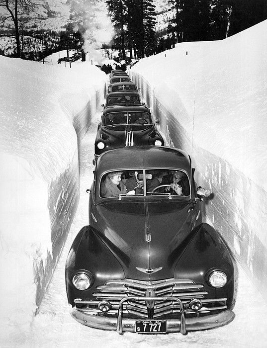 Idaho c. 1952. It's slow going through a plowed cut in the mountains of Idaho.