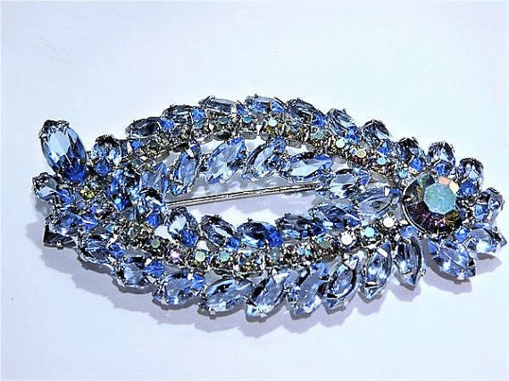 ITEM # 121622  Beautiful, circa 1960s rhinestone brooch. Verified Juliana D & E ! This would be great for something old or something blue for the bride!  This gorgeous piece consists of a large blue faceted glass 12mm closed back round with aurora borealis finish. There are two rows of navettes. Each row consists of navettes with small blue aurora borealis rounds in the middle, and then a larger navette on each end. There are a total of 41 open back blue faceted glass 10mm navettes, 2 open…