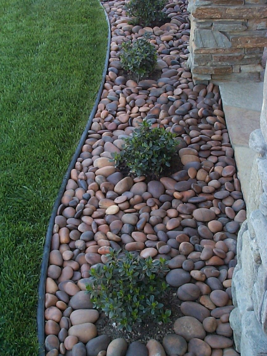 Landscaping with gorgeous polished river rocks a lot of different colors to play with