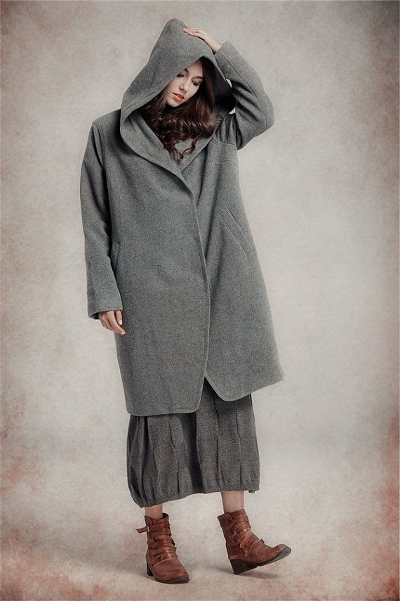 8ea12c17a3b Hooded wool coat in grey. The design of this wool midi coat is simple yet  dramatic at the same time with its oversized draped hood