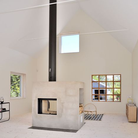 This house situated in an old fishing village in Sweden features pale pine  floors, high ceilings and a wood-burning stove inside a concrete block. - Sandell Sandberg _ Swedish Loftlike House With Fireplace Cozy