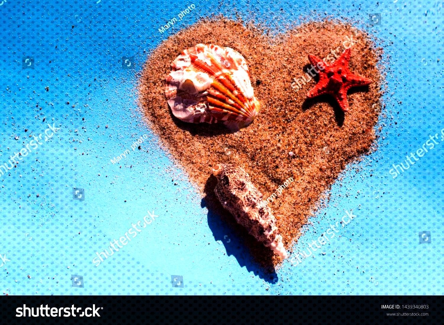 colored shells and a heart of sand on a blue paper texture. Joyful concept of leisure, holidays and