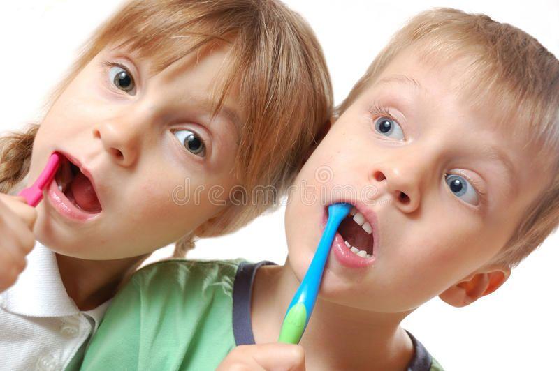 Brushing teeth children. Two cute kids brushing their
