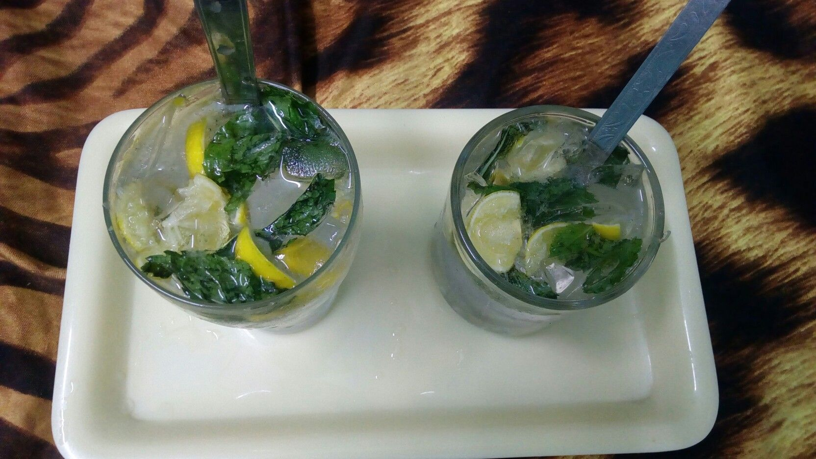 Mojito classic .   • Mint leaves and lemon slices crushed together and with added sugar syrup tastes awesome when completed n poured with soda and ice cubes .