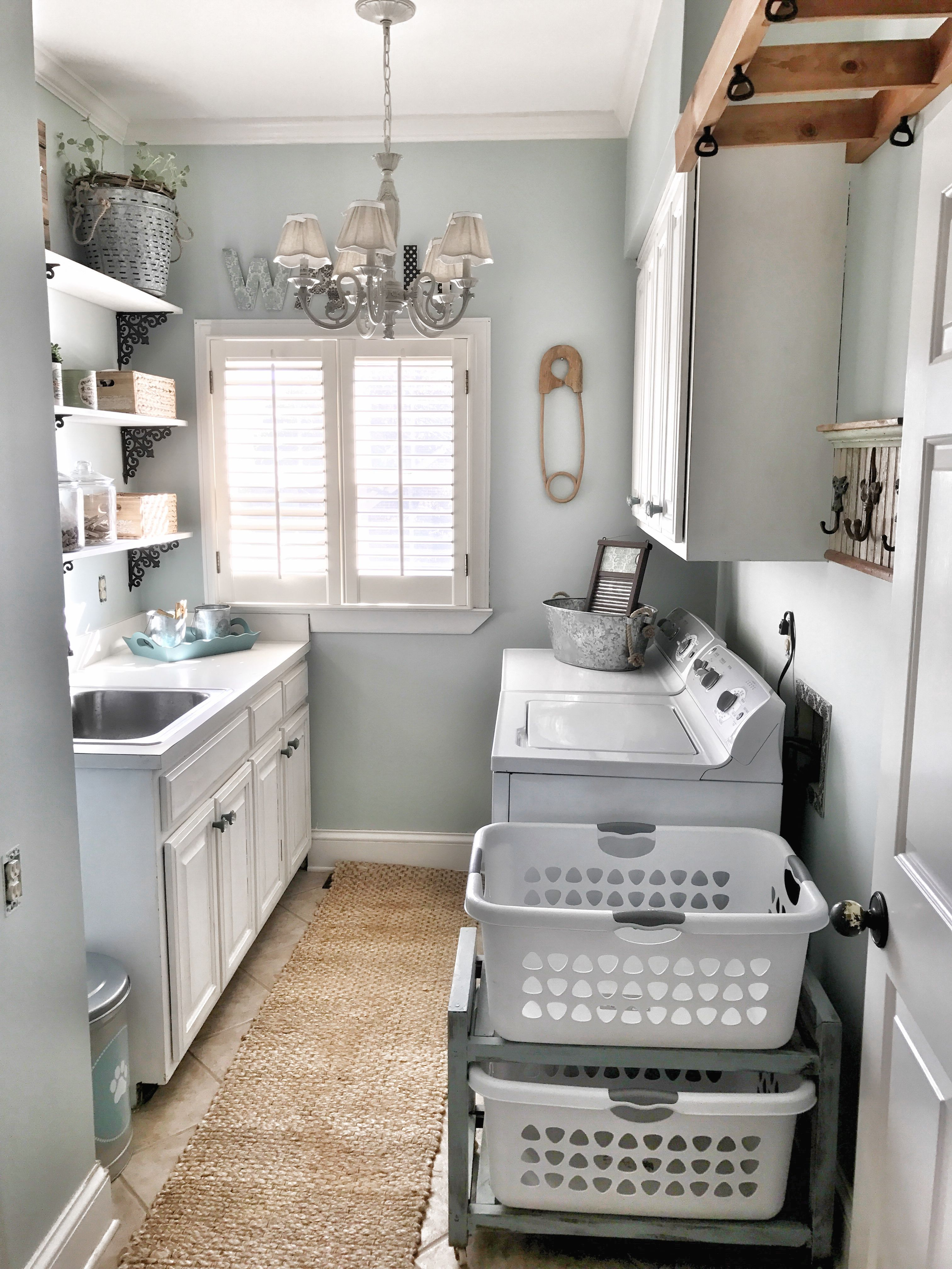 I love every detail of this space the runner hooks on the wall beautiful light fixture white cabinets blue walls all of it