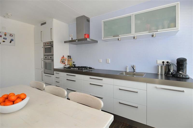 De keuken over de gehele lengte van de wand stijl keuken