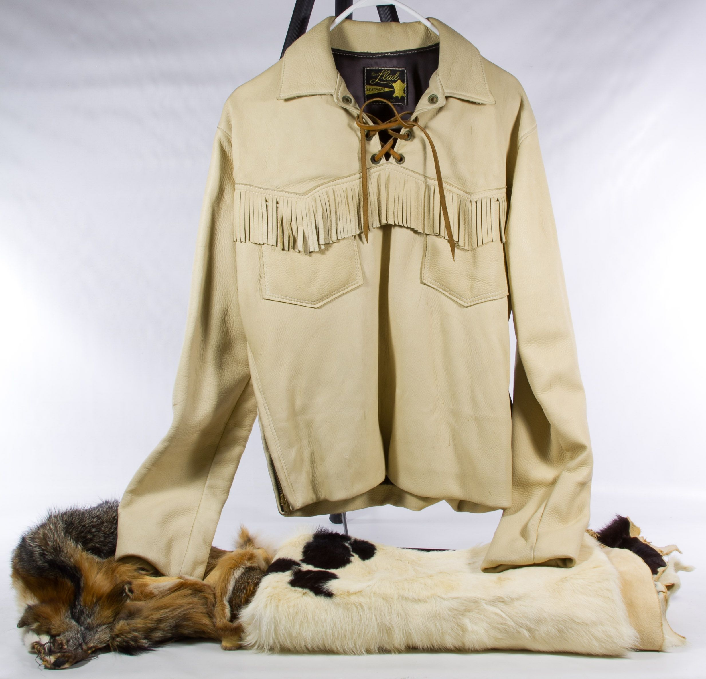 Lot 488: Buck Skin Jacket and Fur Pelt Assortment; Including a Tony Llad fringed and zippered buckskin shirt jacket, a small cow hide and a fox hide
