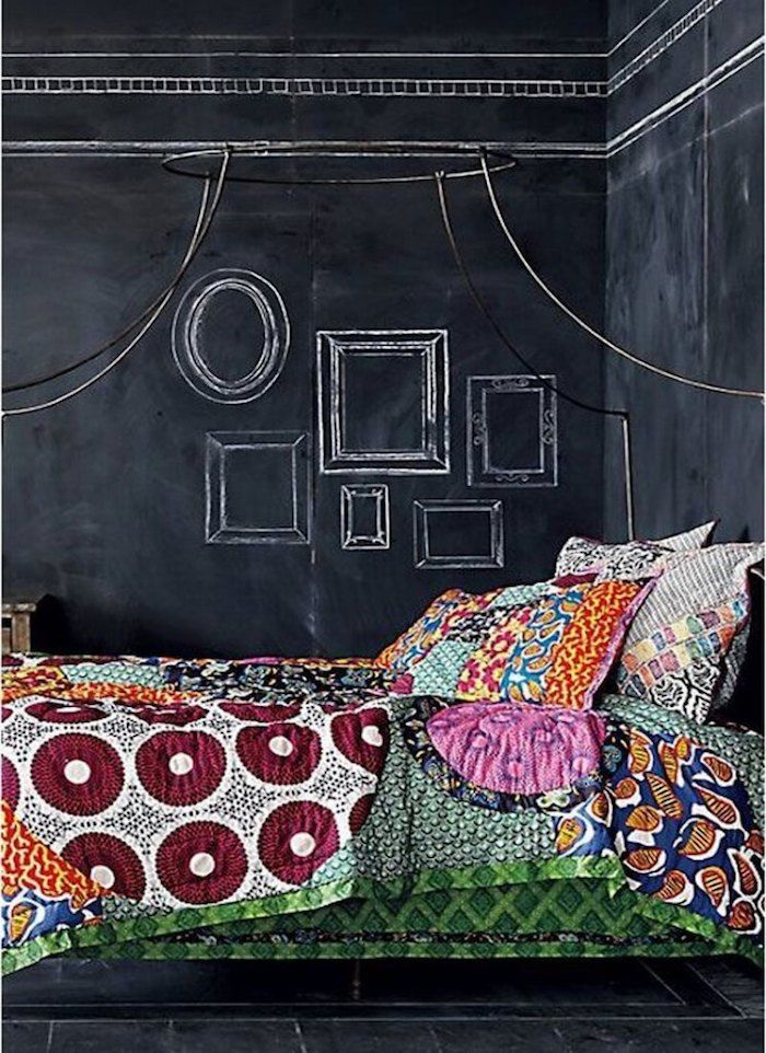 eine Wand mit Tafellack, darüber Bilderrahmen bemalt, ein Bett mit ...