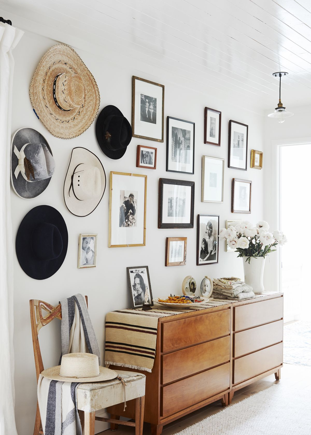 A collection of hats and a gallery wall surround a wooden dresser