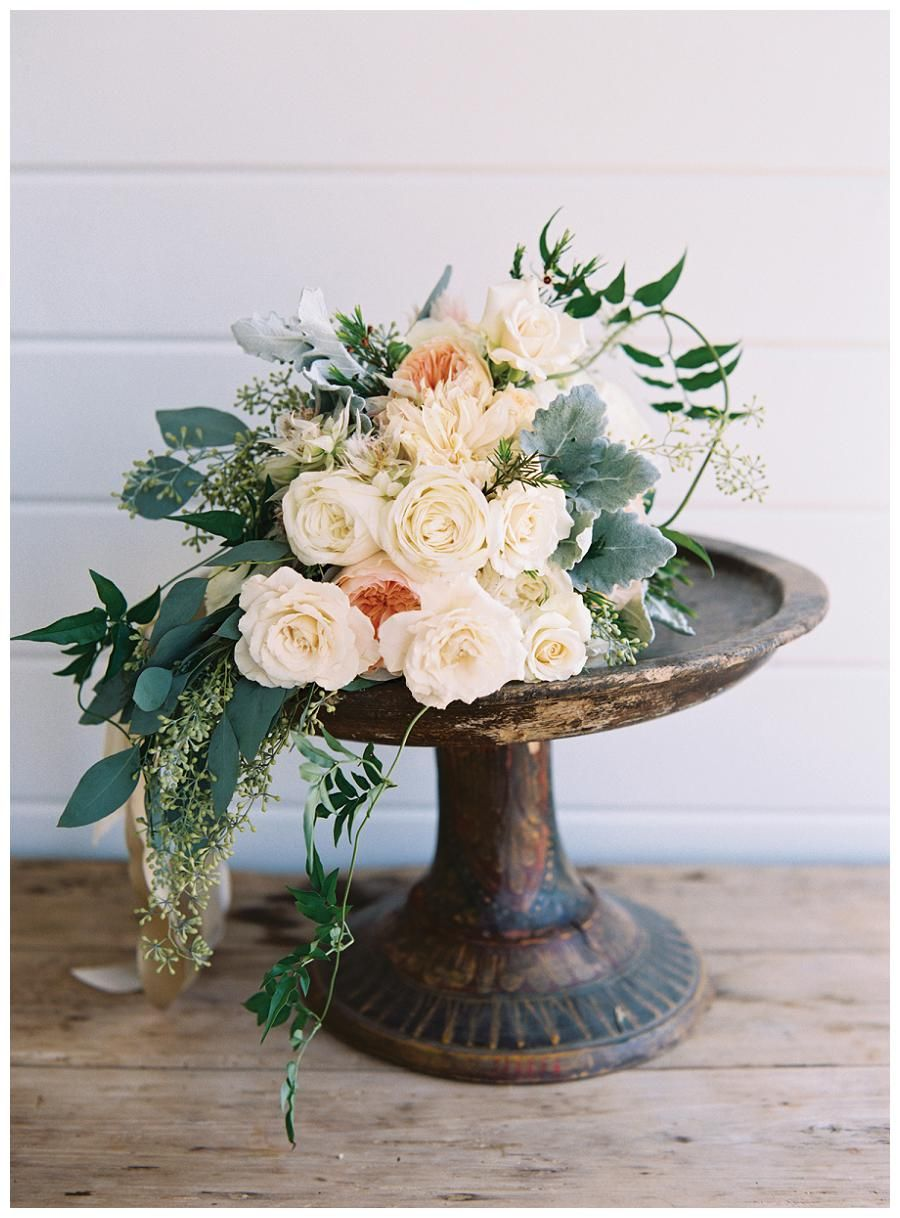 Peach & Cream Rose Bridal Bouquet resting on a wooden cake