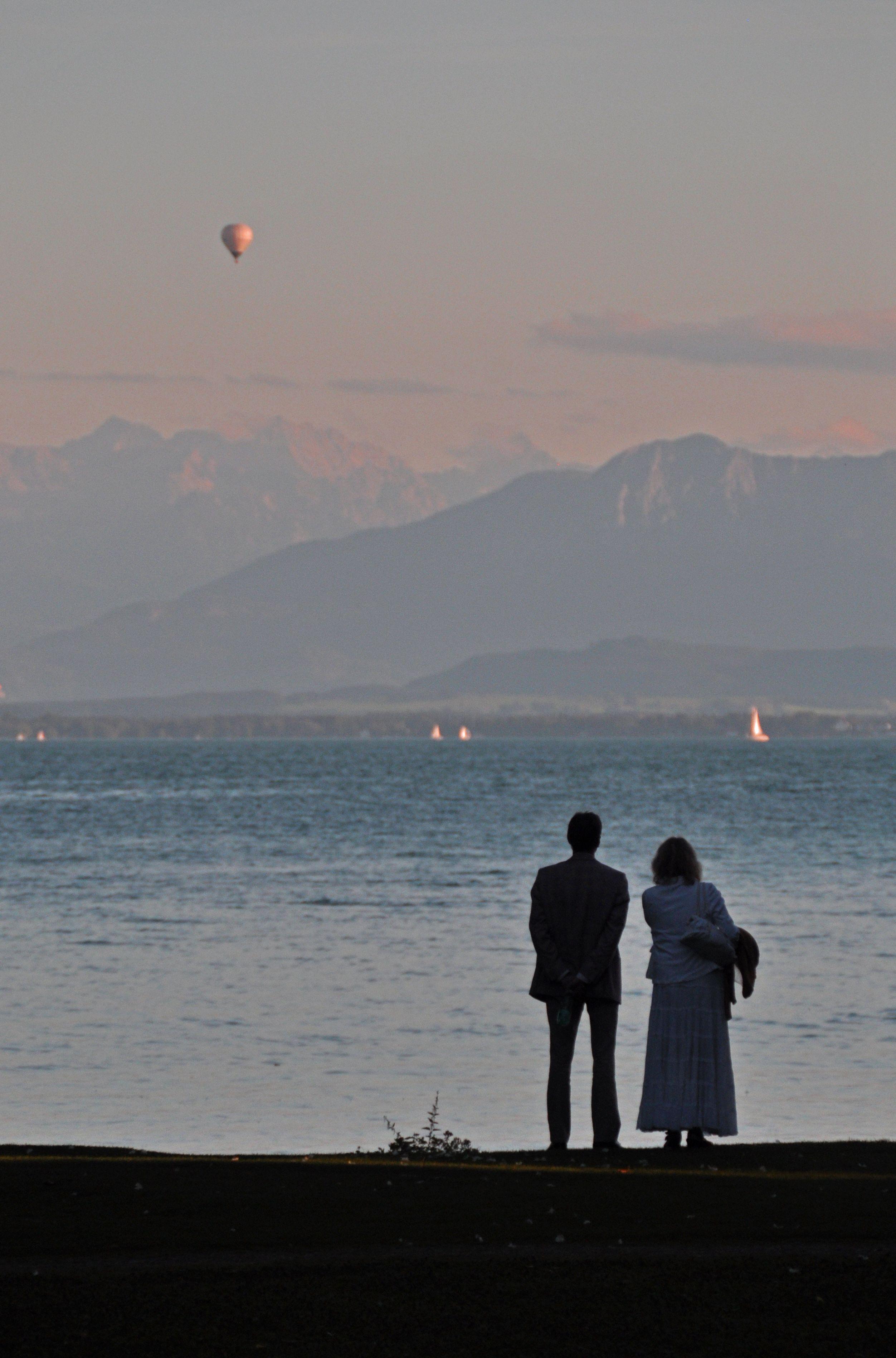 Ein Paar genießt die Abendstimmung auf der Roseninsel it fantastischem Blick auf die Alpen bei Sonnenuntergang
