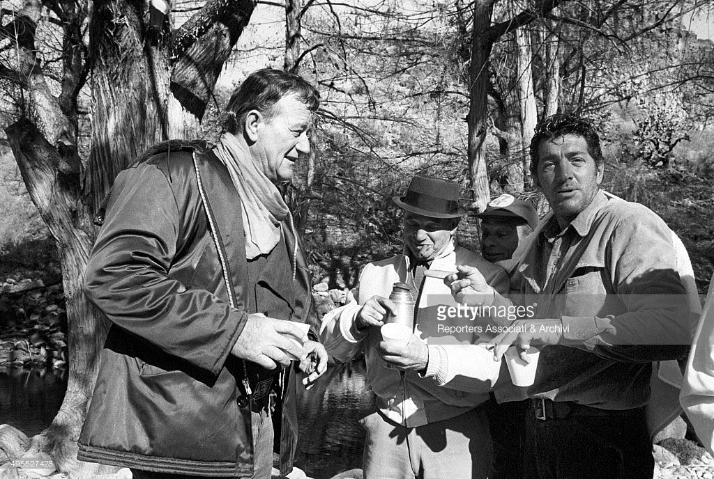 American actor John Wayne and American actor Dean Martin having a coffee under the trees during a break on the set of the film ' The Sons of Katie Elder'. Description from gettyimages.com. I searched for this on bing.com/images