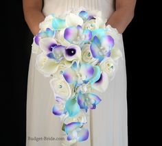 Cascading brides bouquet with orchids tipped in turquoise and purple, purple picasso lilies and white roses with turquoise diamond centers.