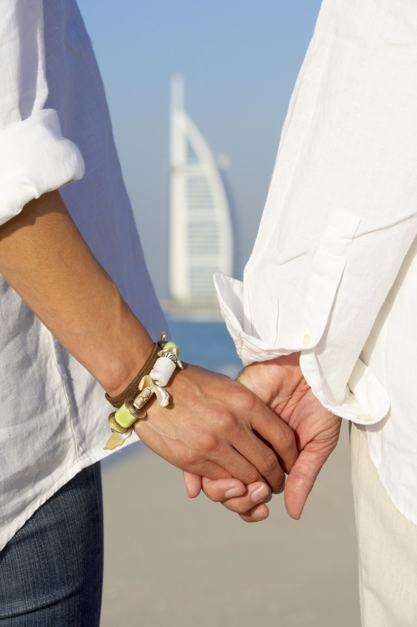 Couple holding hands on beach, Dubai, United Arab Emirates