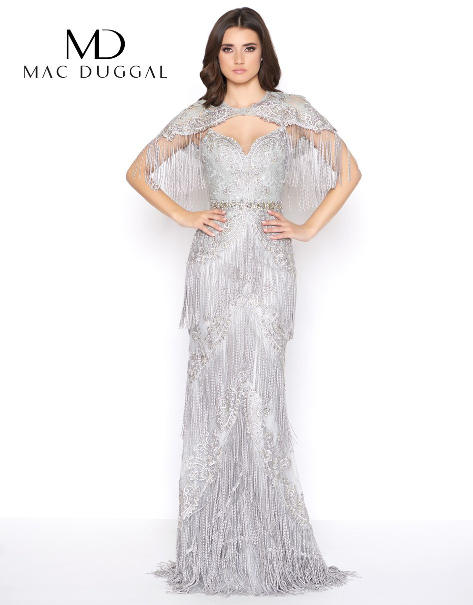 1bcbb789 This elegant lace and fringe layered gown is detailed with scattered  rhinestones throughout the gown, a short lace cape and rhinestoned belt.