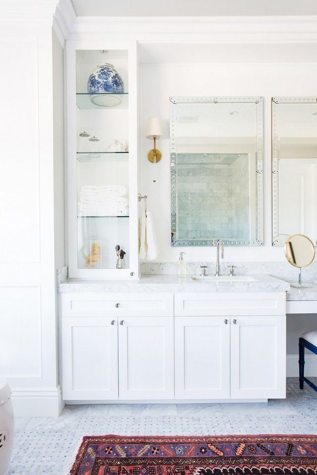 Bathroom with white tiled floors, a Persian area rug, and a marble sink