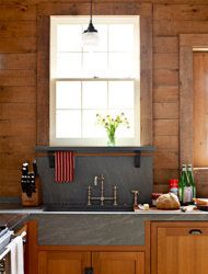 In keeping with this kitchen's origins as a stable, designer Mick De Giulio used warm, rustic materials with pleasing contrasts, like the soapstone countertop (with integrated sinks) and wood cabinets and walls.