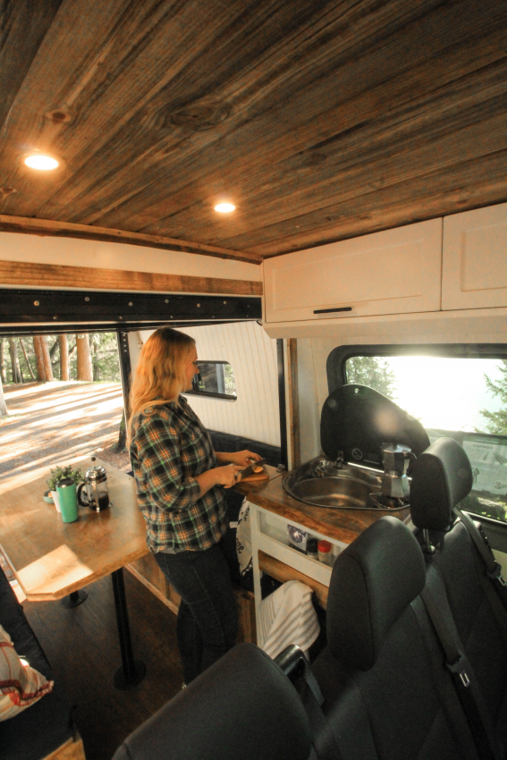 Small kitchen galley makes a great spot for preparing snacks on the road! #van #vanlife #kitchen #kitchengalley #familyvan #sprintervan #sprinter #sprinter144 #convertedvan #vanconversion #freedomvans #sprinterconversion #vanideas #vangoals #convertedsprinter #glamping #glamping #aesthetic