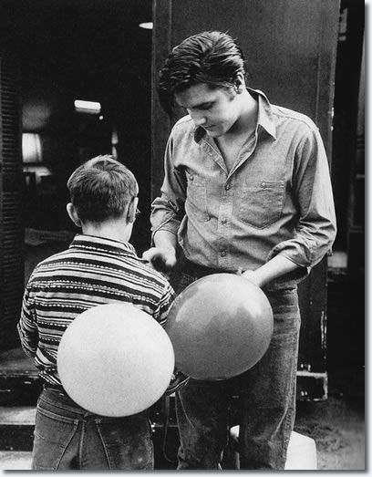 Elvis signing autographs on the set of Loving You. -