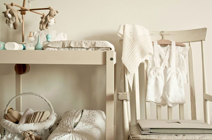 Cream baby changing table with paraphernalia and cream chair - Getty ...