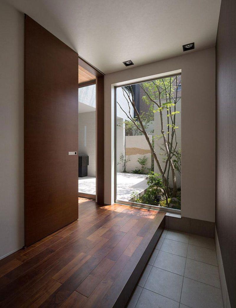 Moderna casa de dos plantas con fachada de madera e for Disenos de puertas para interiores