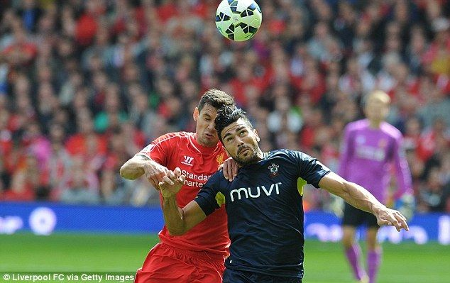 Jumping for joy: Lovren battles Southampton new boy Graziano Pelle for the ball during Sun...