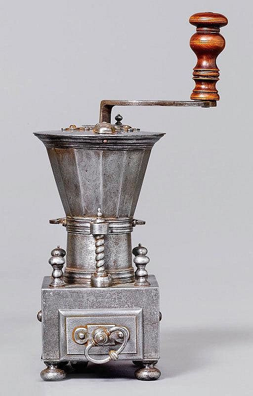 A TABLE TOP COFFEE MILL, France, circa 1700. the inside of the lid marked R.MARTIN. Cone-shaped hopper on rectangular body with drawer for grinds. The screw clamp with fleur-de-lys decoration.