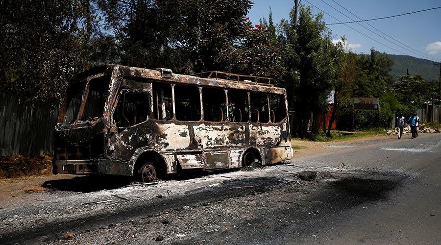Men walk past a bus that was torched during protests in the town of Sebeta, Oromia region, Ethiopia, October 8, 2016. ©Tiksa Negeri