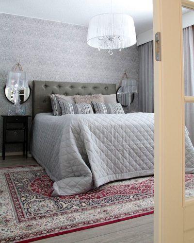 Punertava iso matto makuuhuoneen sängyn alla tuo lämmintä tunnelmaa sisustukseen. Huomaa myös Kartell Bourgie valaisimet yöpöydillä sekä hauskat ympyrän muotoiset peilit.