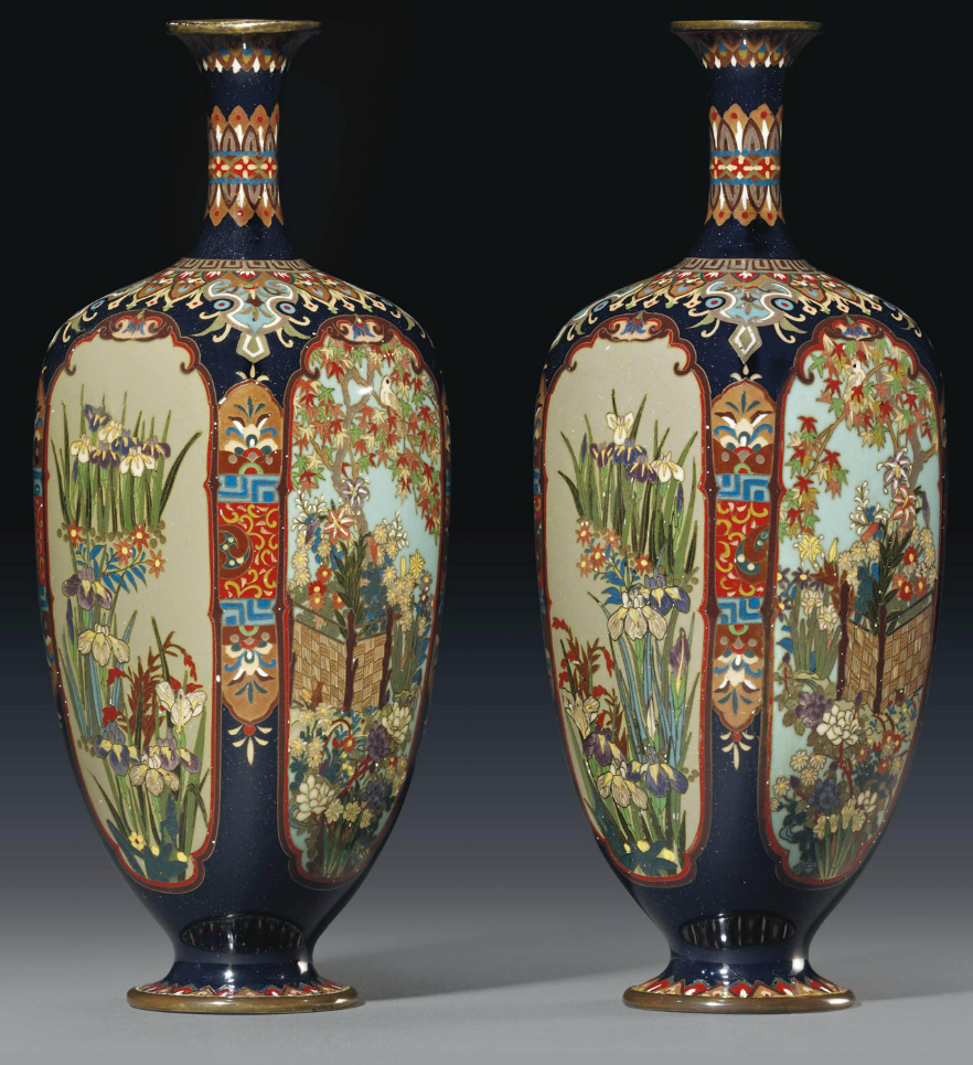 A Pair of Cloisonné Vases Meiji Period (late 19th century) Each worked in copper wire and various coloured cloisonné enamels with four lobed panels containing maple trees and flowers behind wood fences and irises, bordered by stylised flowers and geometric patterns on a deep blue ground, copper rims