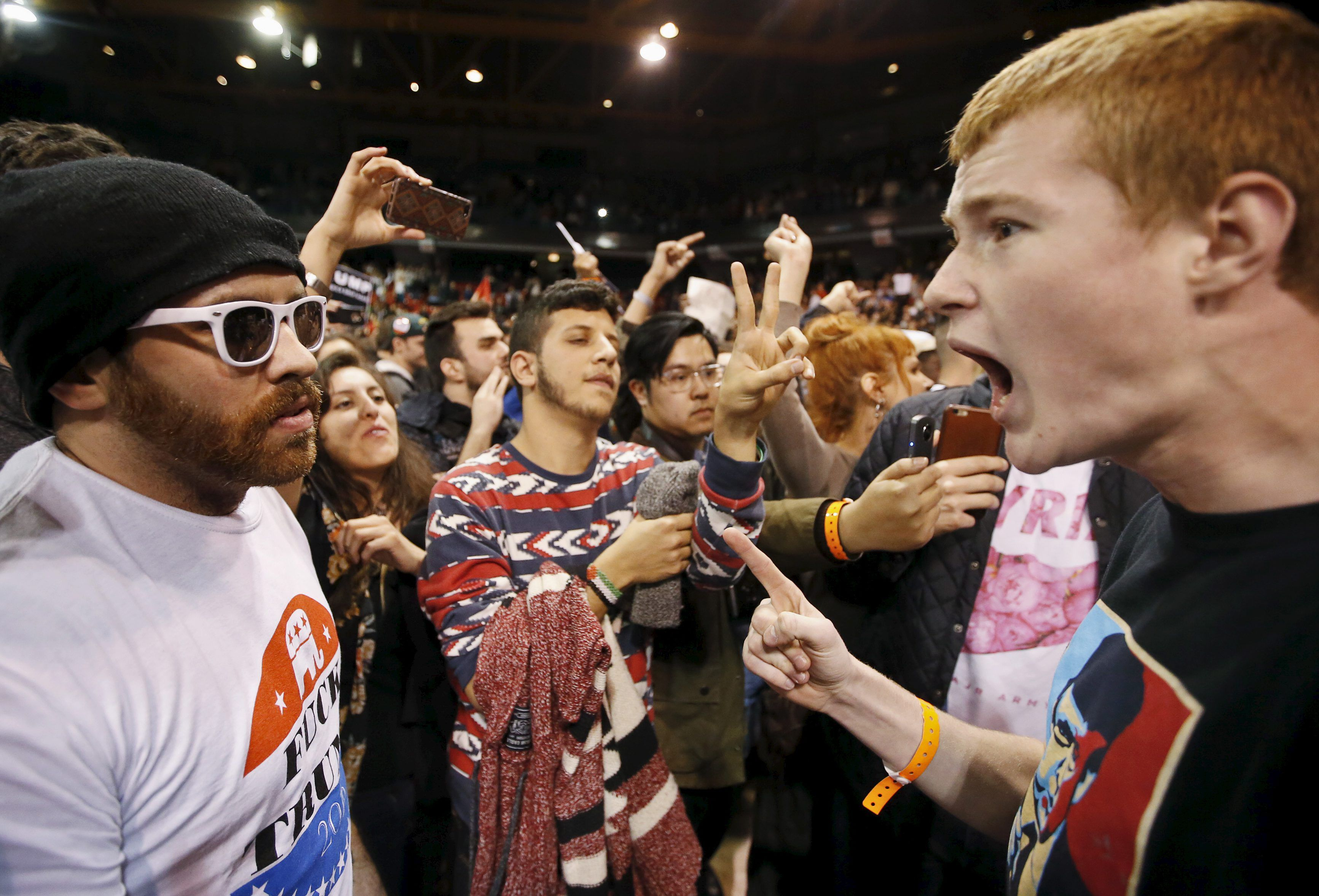 A Trump supporter (R) yells at a demonstrator (L) after Republican U.S. presidential candidate Donald Trump cancelled his rally at the University of Illinois at Chicago March 11, 2016.