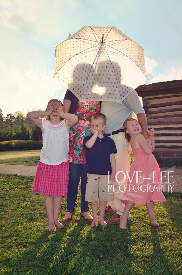 Kissing behind an umbrella family photo. love-leephotography.com