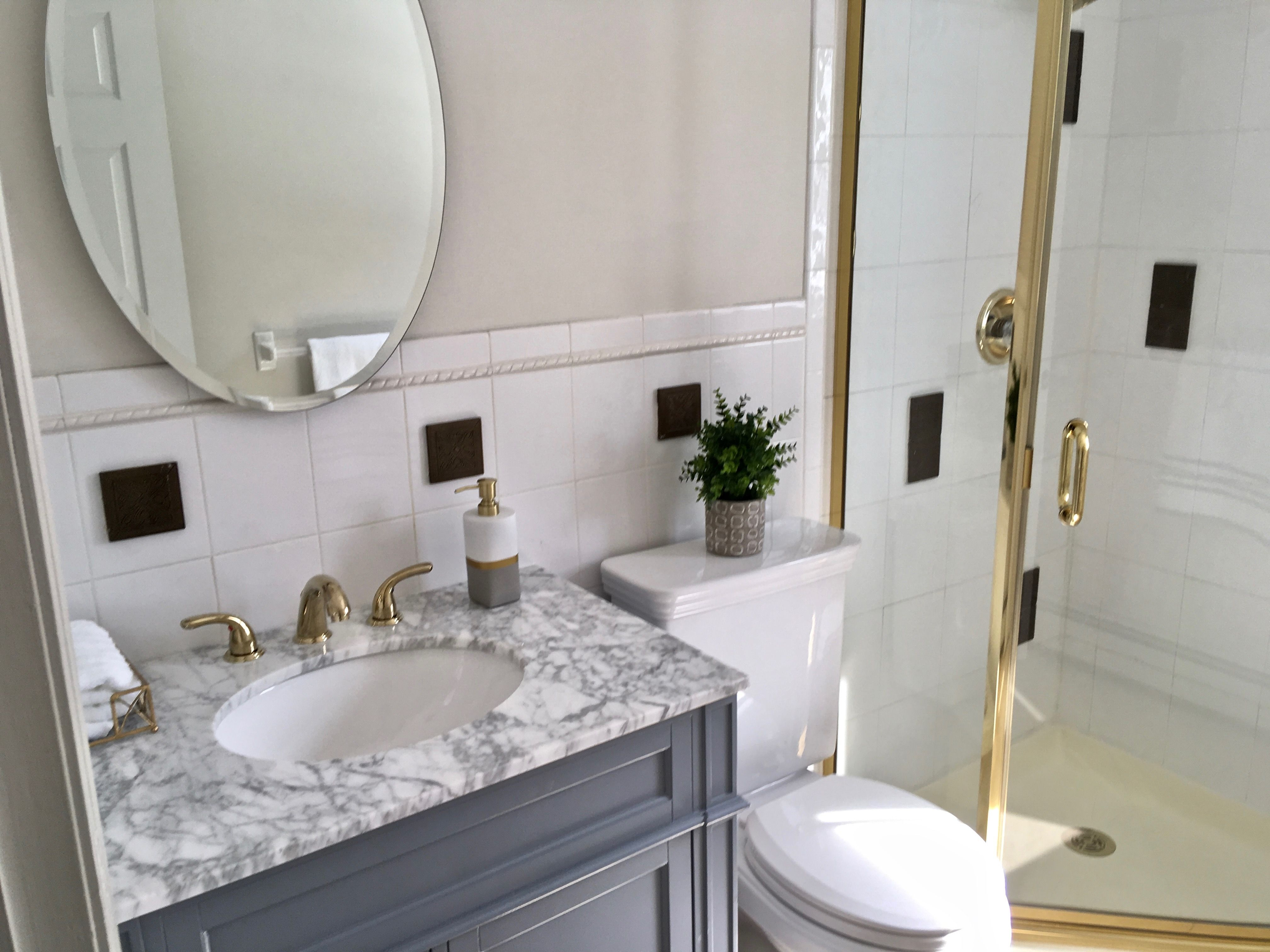 One way to make shiny brass look more updated in a bathroom: swap ...