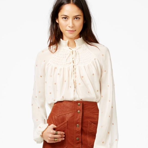 Free People  Smocked Blouse Polyester; embroidery: LUREX metallic fibers Machine wash Imported Smocked high neck with self ties, long sleeves, elasticized cuffs Sheer, allover metallic embroidery, smocked front and back yokes Button front partial closure, high/low rounded hem, flowy fit Free People Tops Blouses