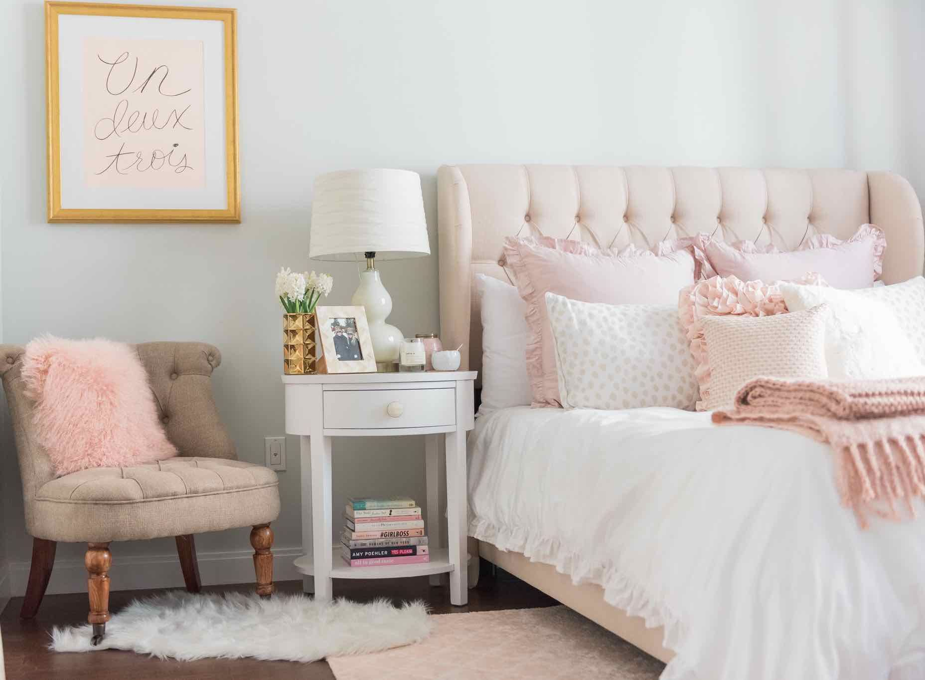 This lush pink bedroom is flushed with soft details including a faux fur  rug and light