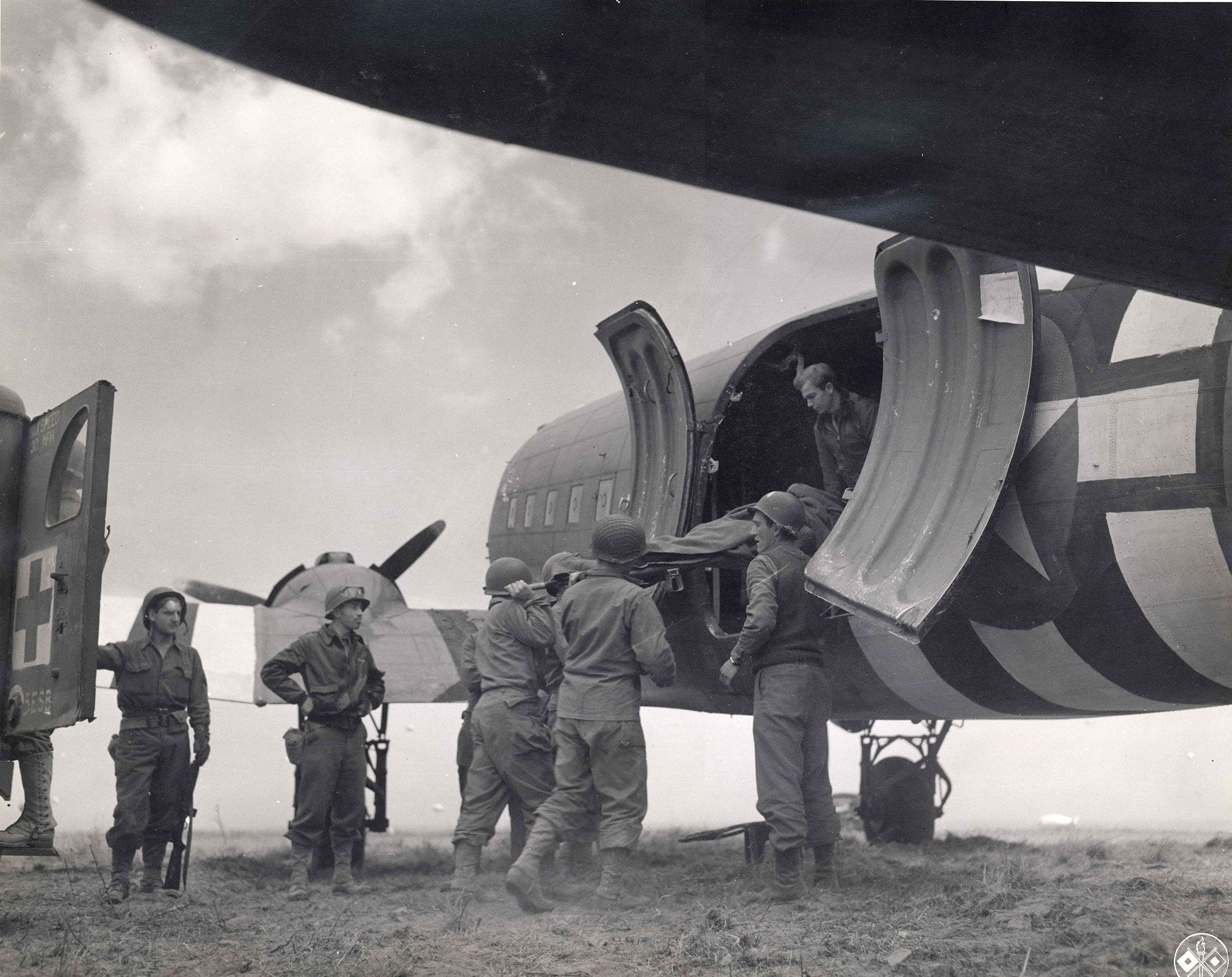 Wounded soldiers are being loaded onto a Douglas C47 for