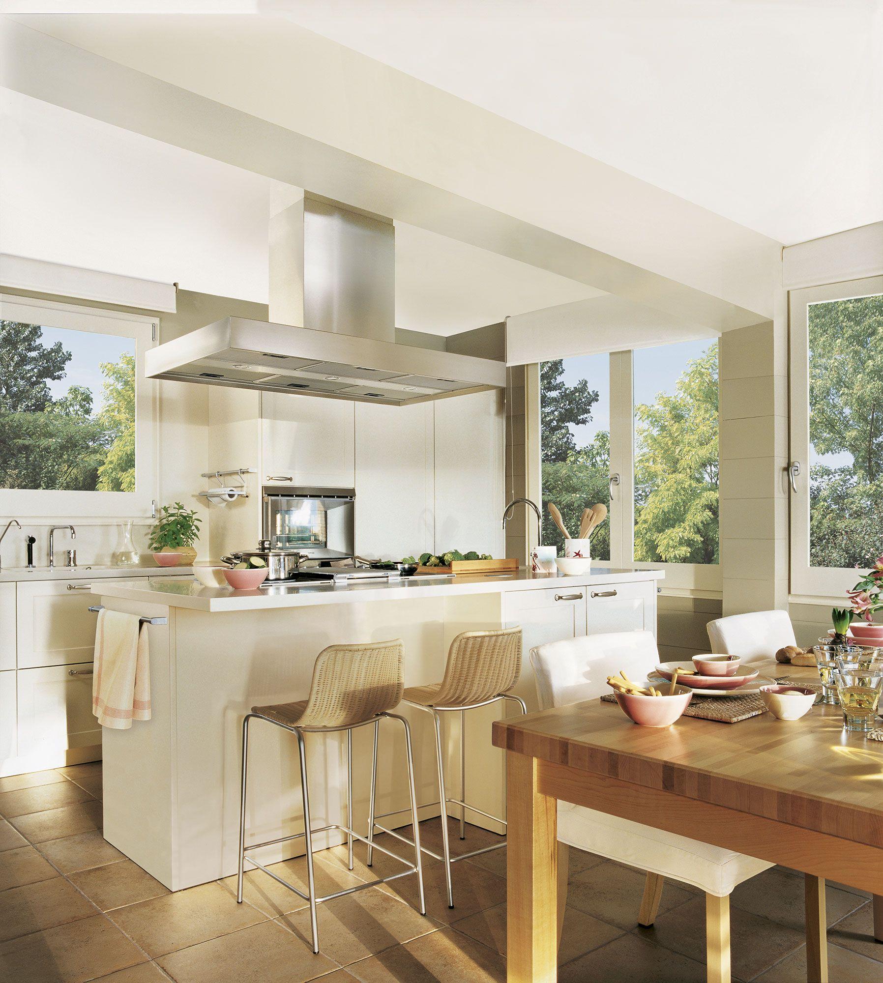 Cocina blanca con isla taburetes de mimbre y mesa de for Isla cocina comedor