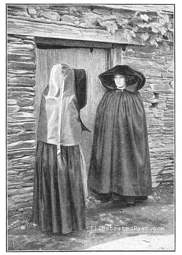 Two women from Brittany wait outside a mourning chamber, where the body of a deceased lies. 1906