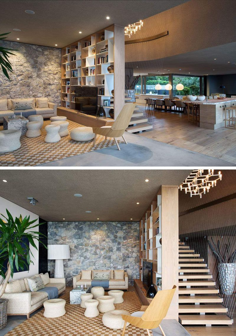 This Living Room Has A Stone Feature Wall And Bookshelf That Separates The From Stairs
