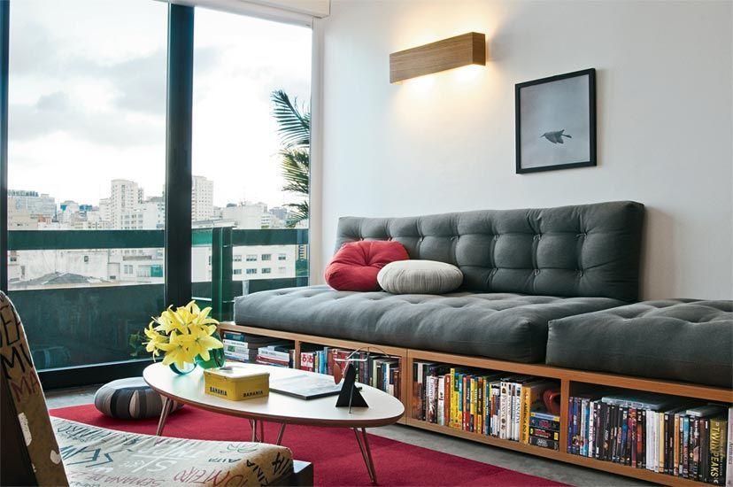 Ideia do arquiteto Antonio Mantovani, o sofá de futon completa uma base de marcenaria para abrigar livros e DVDs, perfeita para espaços pequenos. O cinza-chumbo do estofado dá tempero urbano ao ambiente, que leva piso de cimento queimado. Ambos ganharam pitada certeira de vermelho: na almofada e no tapete.