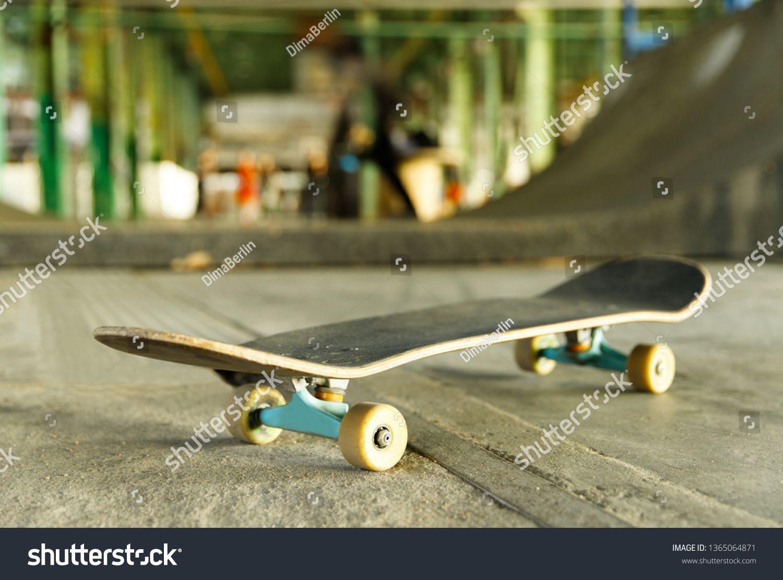 Closeup of skateboard in skateboard park, indoors, blurred