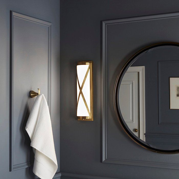 This long brushed brass sconce flanking the bathroom mirror warms up these moody bluish-gray walls.