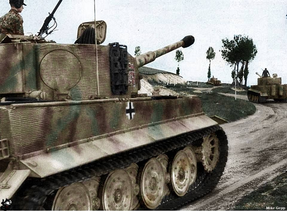 """German heavy tank """"Tiger I"""" of the 101st Heavy Tank Battalion, the SS running along the road 316 to Morgny (Normandy, France), June 7, 1944. The commander of the tank closest to us – Unterscharführer SS Ewald Möli."""