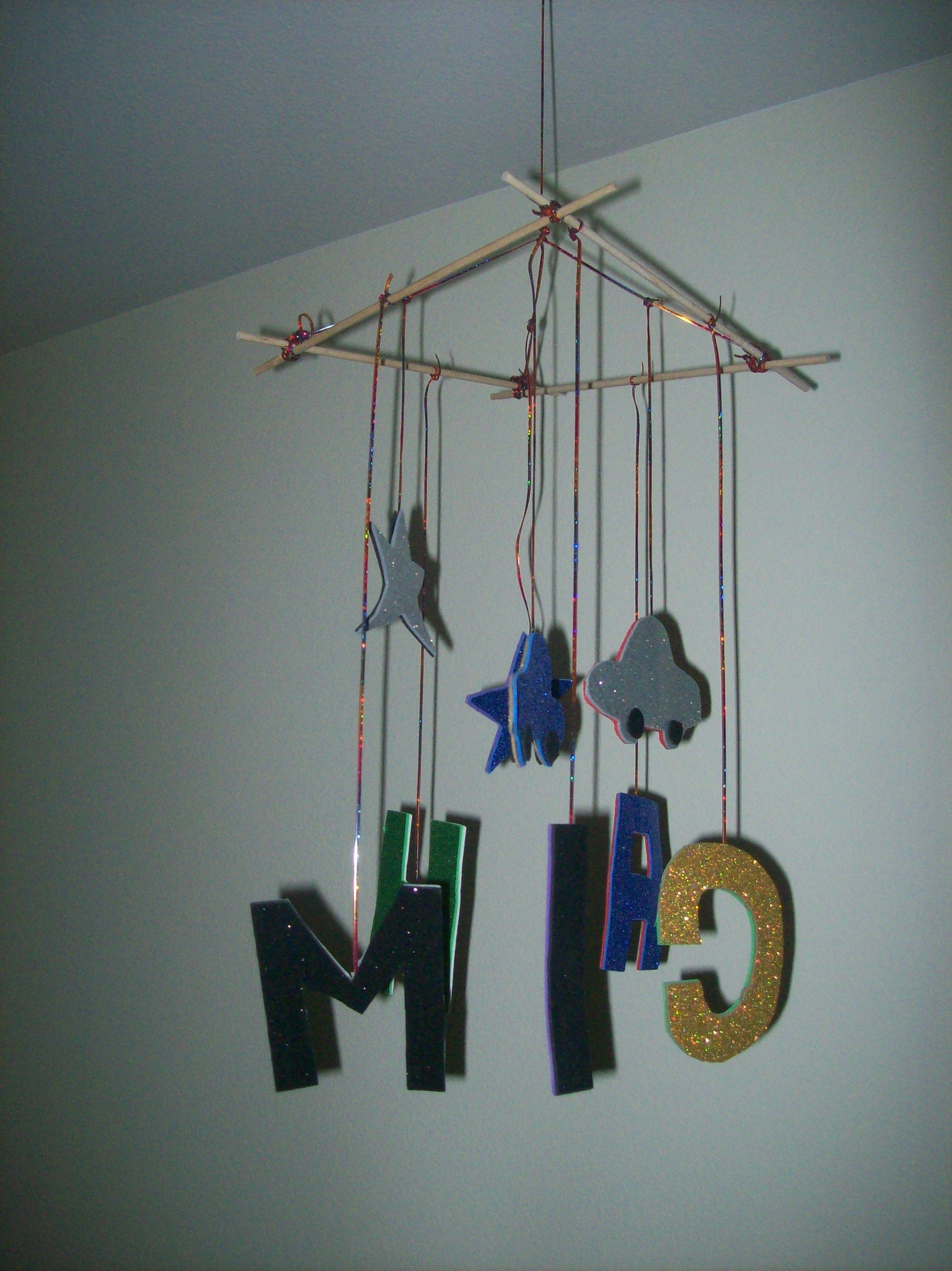 Baby Mobile. Used glitter paper with adhesive back and found colorful twine or string and stuck string in between glitter paper. Hung other end of string on some dowels that i tied together. Super cute and sparkly!