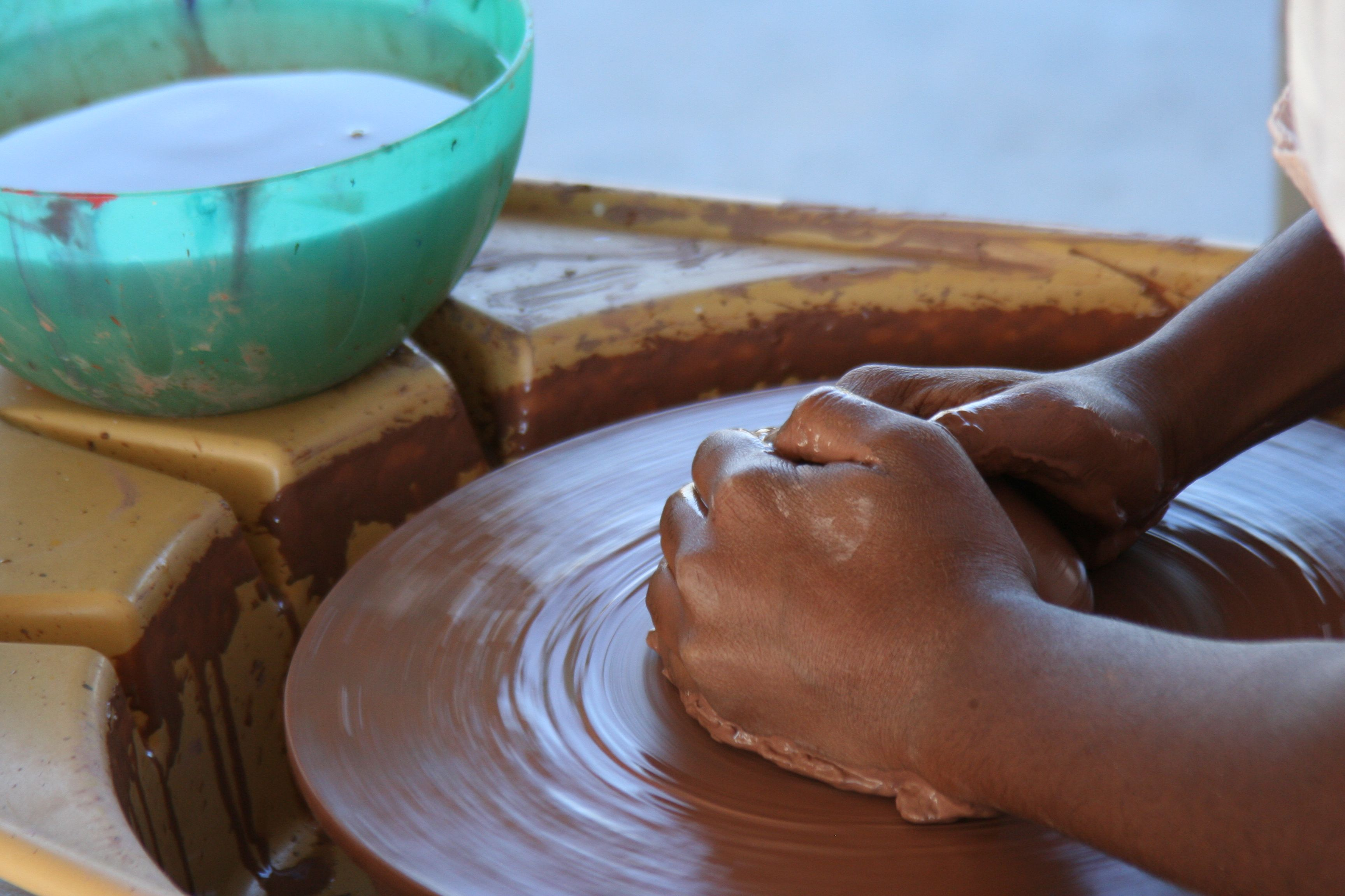 A student works on the pottery wheel outside the
