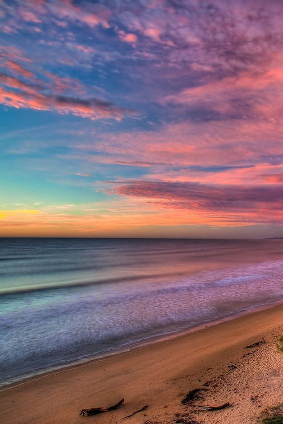 The Sun sets on a beach near Oamaru on the South Island, New Zealand - There are many reasons to visit New Zealand including adventure travel, hiking, water sports and culture, but capturing the beauty of its diverse scenery is what will make your holiday